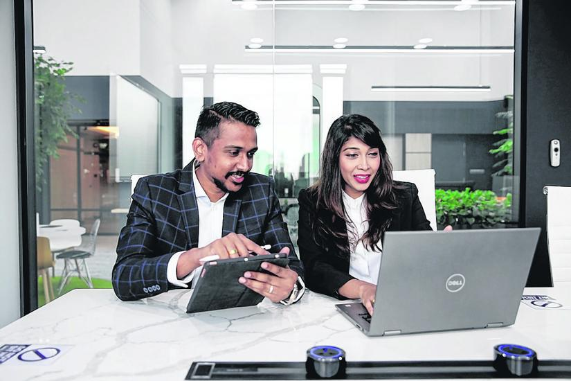 Nesh and Maha pictured using technology to sell houses